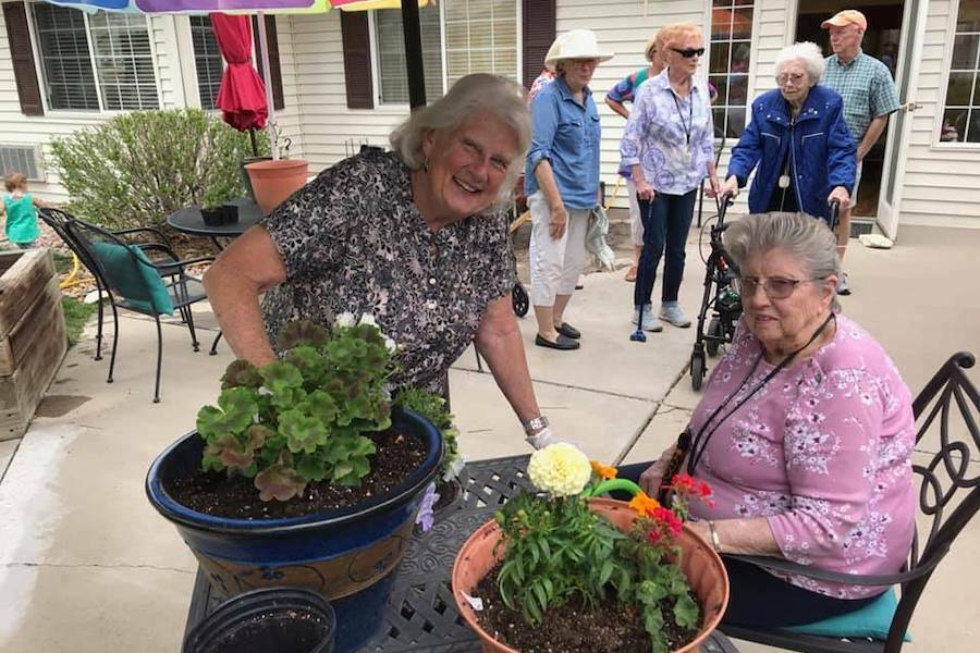 seniors with flowers in planting pots