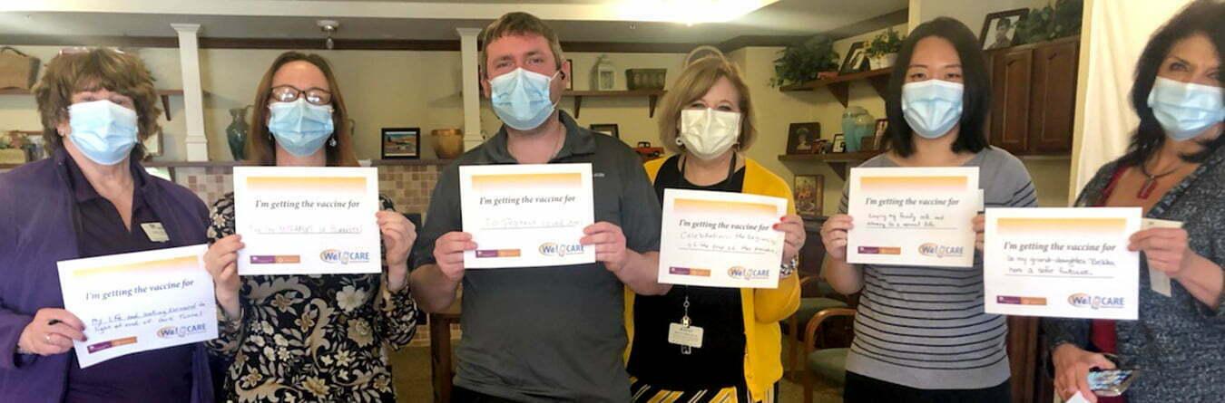 Cappella Pueblo West team members holding vaccine certificates
